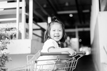 a toddler girl sitting in a shopping cart