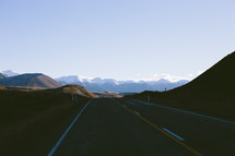 A highway leading toward a mountain range.