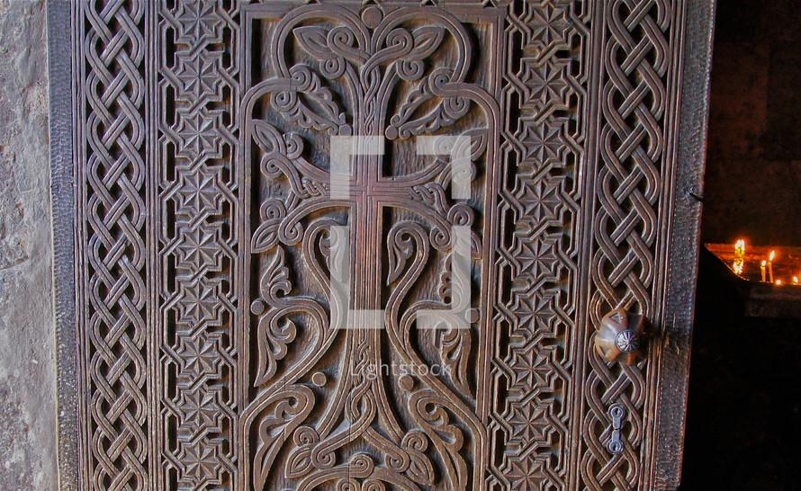 Ornate door open to candlelit room.