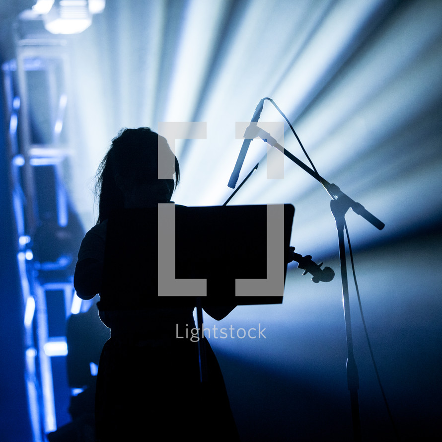 A silhouetted woman playing the violin on stage
