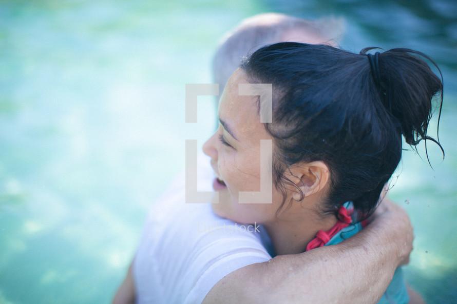 pastor hugging a woman after her baptism