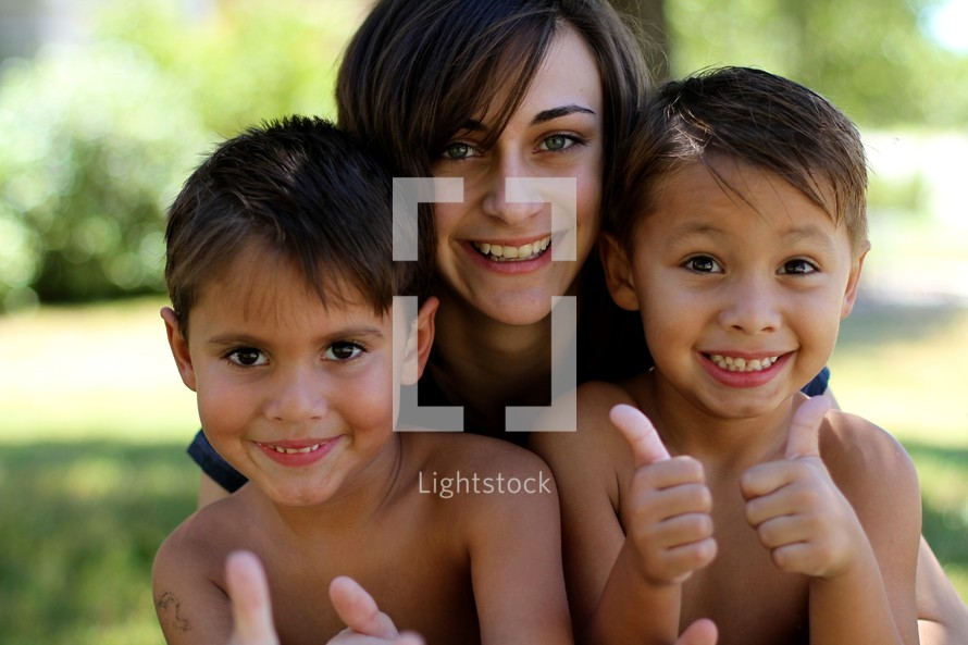 A smiling mother with her two young boys.