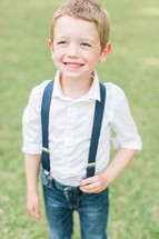a smiling boy child in jeans and suspenders