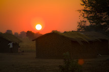 sunset over a thatched roof hut