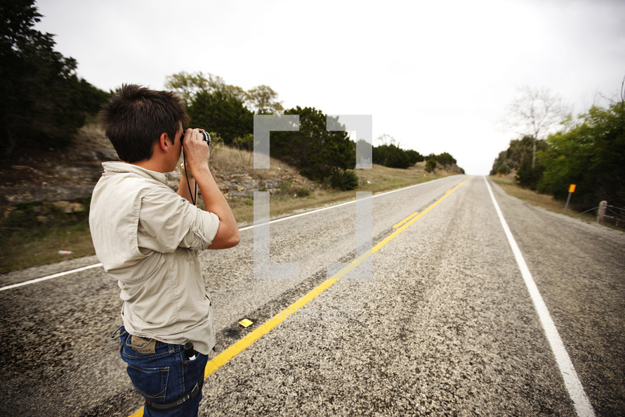 A man takes a picture looking down the highway