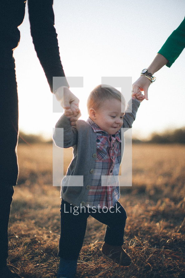 Adult hands holding hands of toddler child while walking in grassy field during the day.