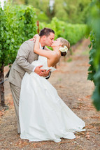 Kissing couple in a napa valley grape vineyard wedding bride groom dip flower in hair