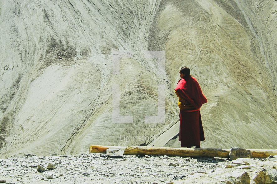 man standing in front of a large sand hill