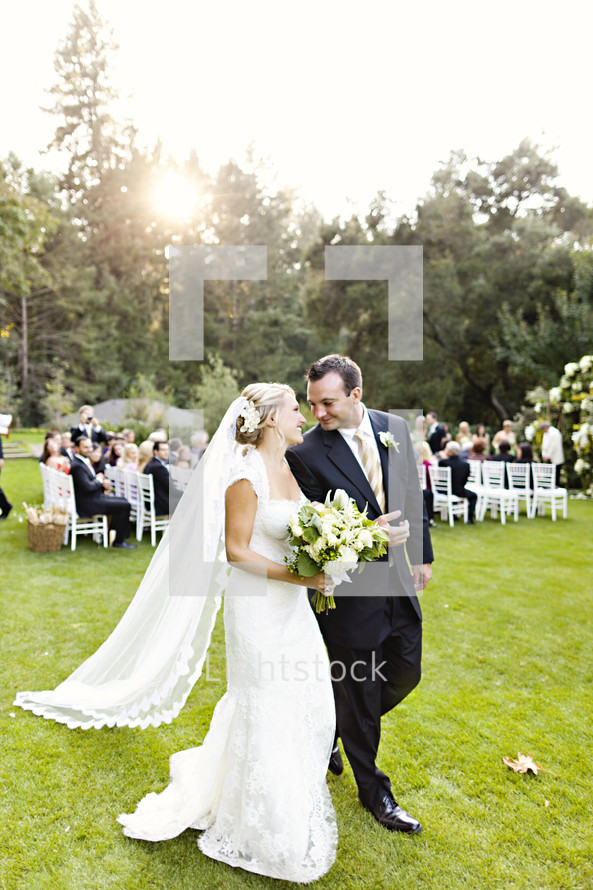 A bride and groom walking together wedding ceremony I do smiling happiness married marriage