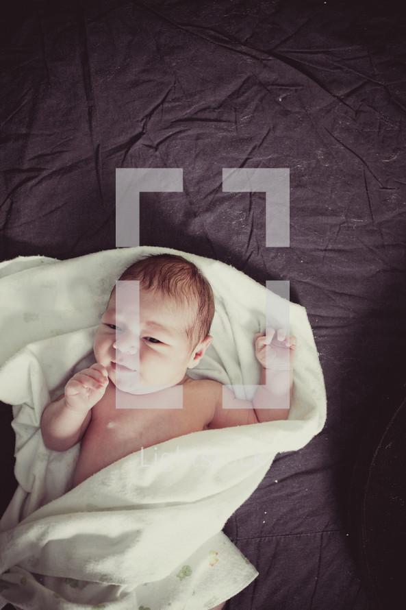infant swaddled in a blanket