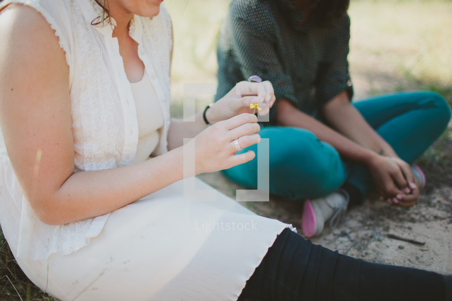 Woman sitting and talking with teen outdoors