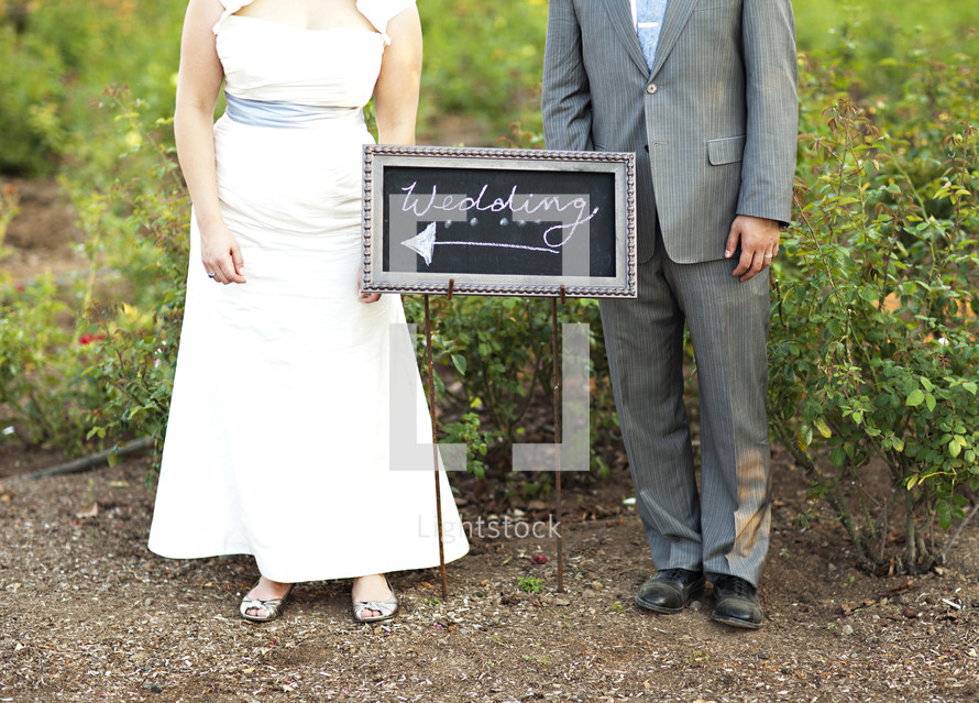 bride and groom standing in front of a sign with the words WEDDING