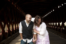 Couple laughing together on a covered bridge.