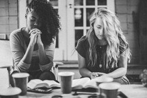 women in prayer above open Bibles at a Bible study