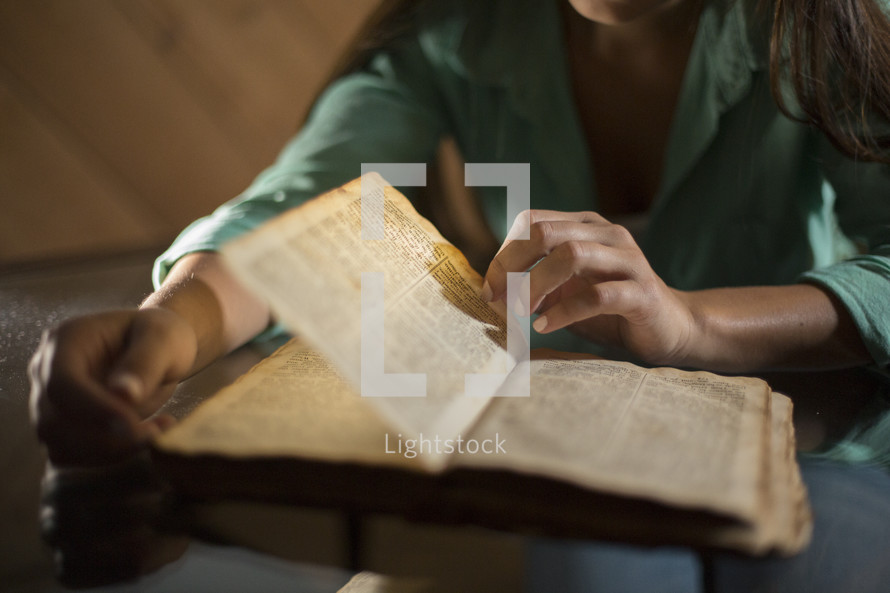Girl turning pages of Bible on top of table.