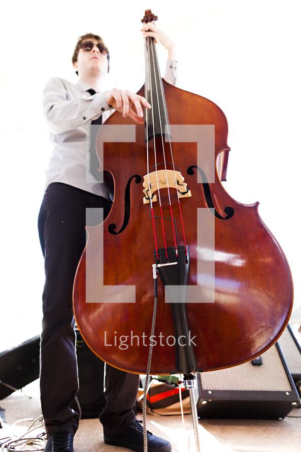 A musician playing a stand up  bass.