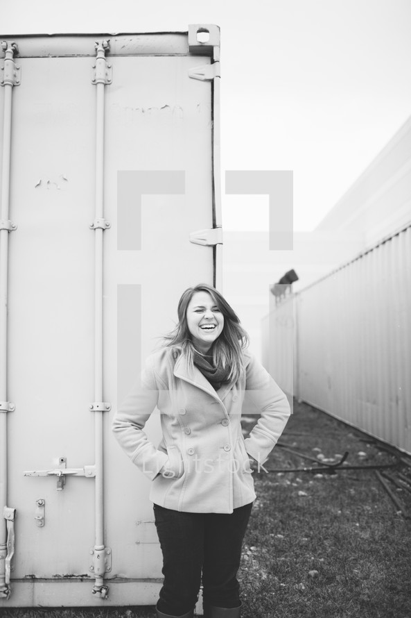 woman in a coat standing in front of storage bins
