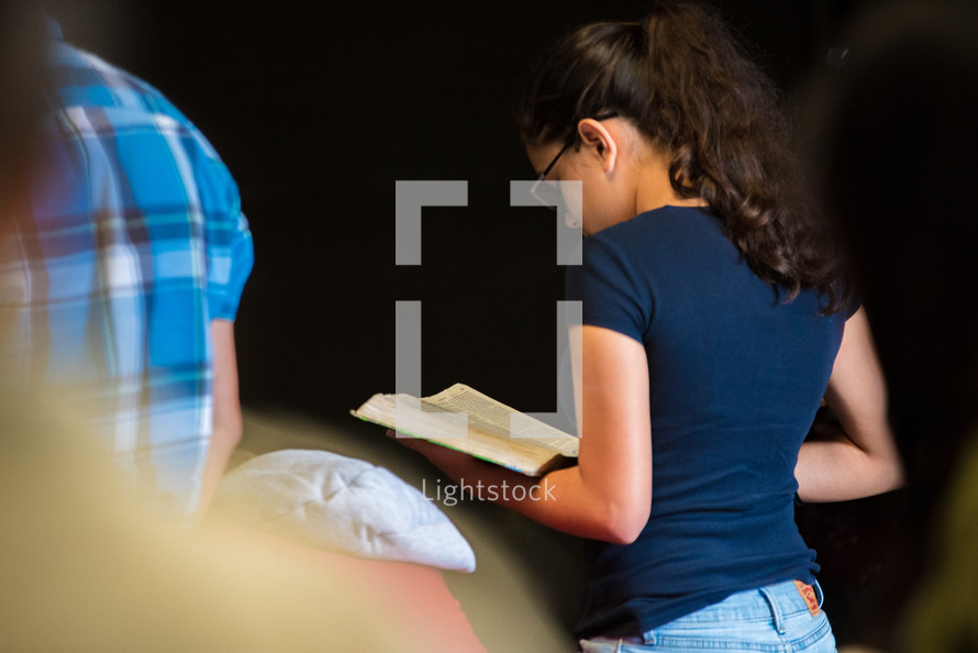 a teen girl holding a Bible during a worship service