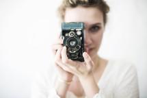 Woman looking through a vintage camera.