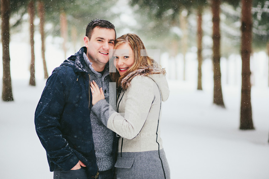 a couple hugging in the snow