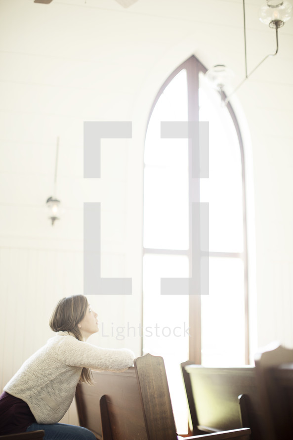a woman looking up to God sitting in a church pew