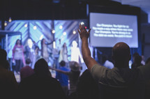 audience with raised hands singing along with worship leaders