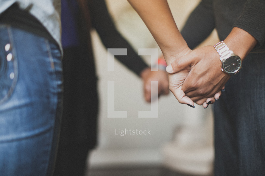 holding hands in a preyer circle