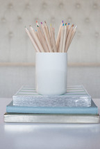 colored pencils in a ceramic cup on a stack of books