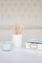 candle, cup, colored pencils, journal, notebook