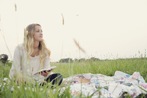 woman reading a book outdoors on a blanket in the grass