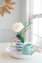 rose in a vase, and mug on a ceramic tray