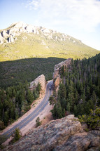 A car on a highway through rocky hills.