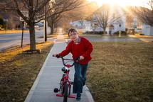 a boy riding a bike on a sidewalk