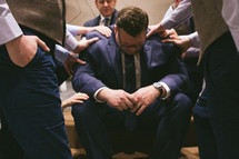 A groom praying before his wedding.