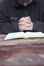 man with praying hands over the pages of a Bible