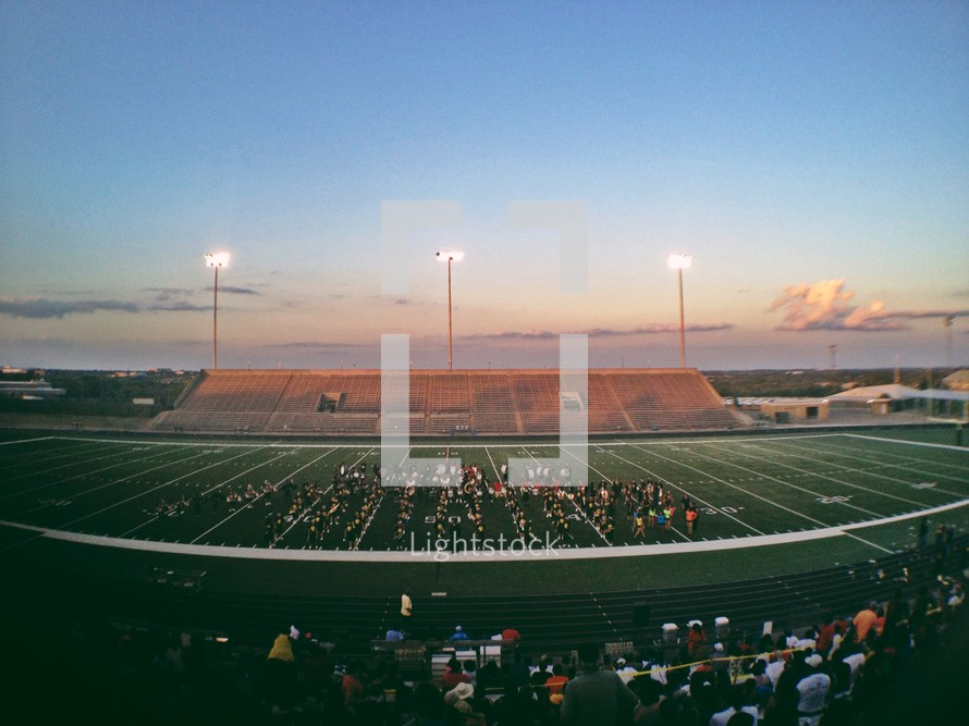 Panoramic view of lighted football field from sideline at dusk.