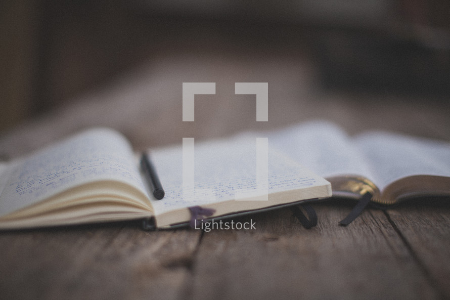 An open Bible, notebook and pen on wood