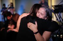 women hugging during a worship service