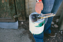 Person holding a old paint can and brushes