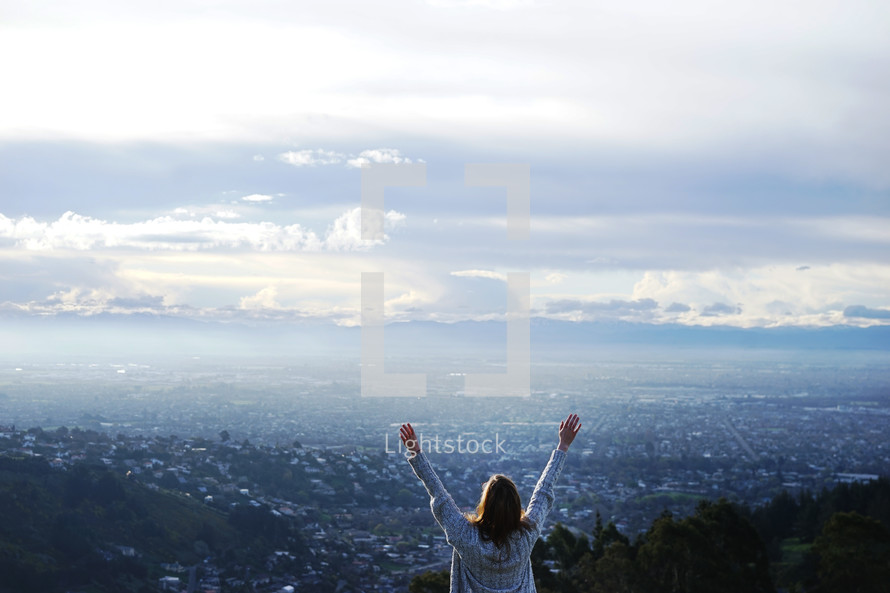 raised hands of a woman looking out over a view of the suburbs