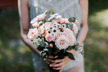 a woman holding a bouquet of pink roses