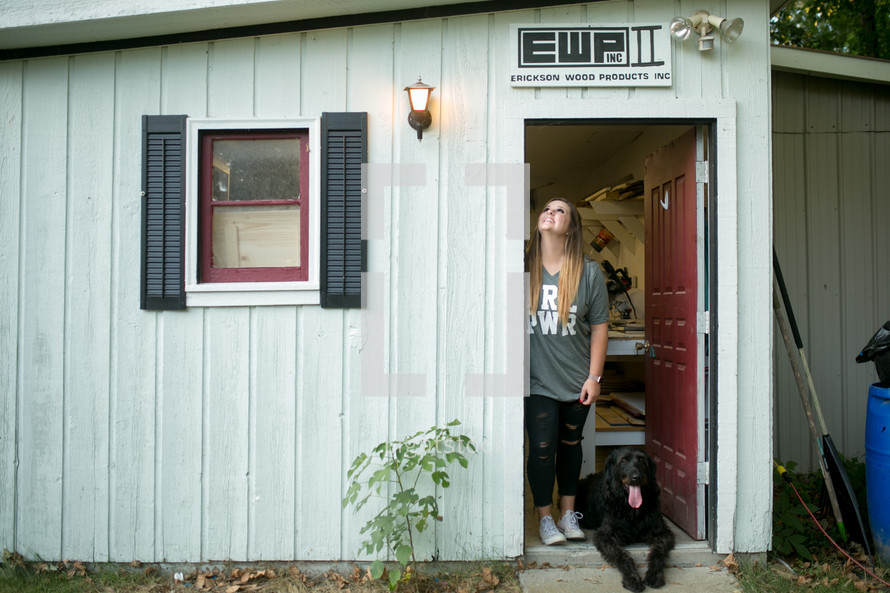 a young woman in the doorway of a workshop