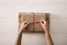 Tying a red ribbon on a wrapped gift.