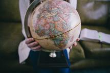 A woman sits holding a globe.