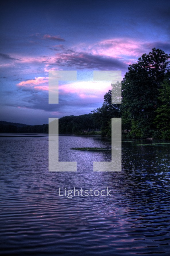 pink and purple clouds over ripples in lake water
