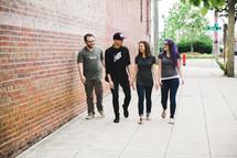 friends walking on a sidewalk talking
