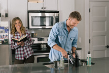 man washing dishes in the sink and a woman reading a Bible