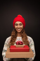 a woman holding a stack of Christmas gift boxes