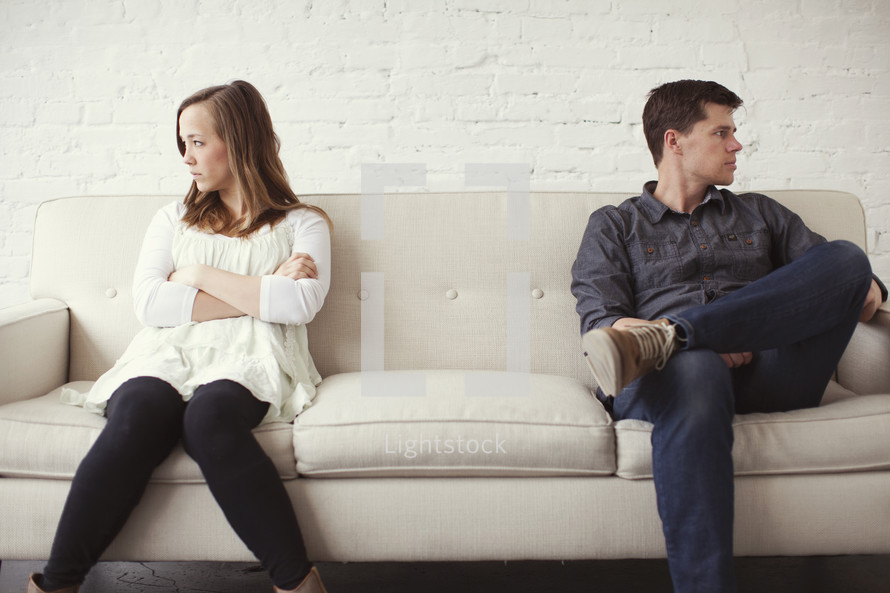 Estranged couple sitting on a couch after an argument.