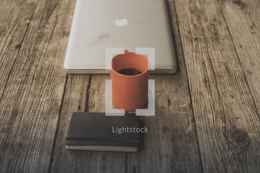 A laptop, notebook and coffee on a wooden table